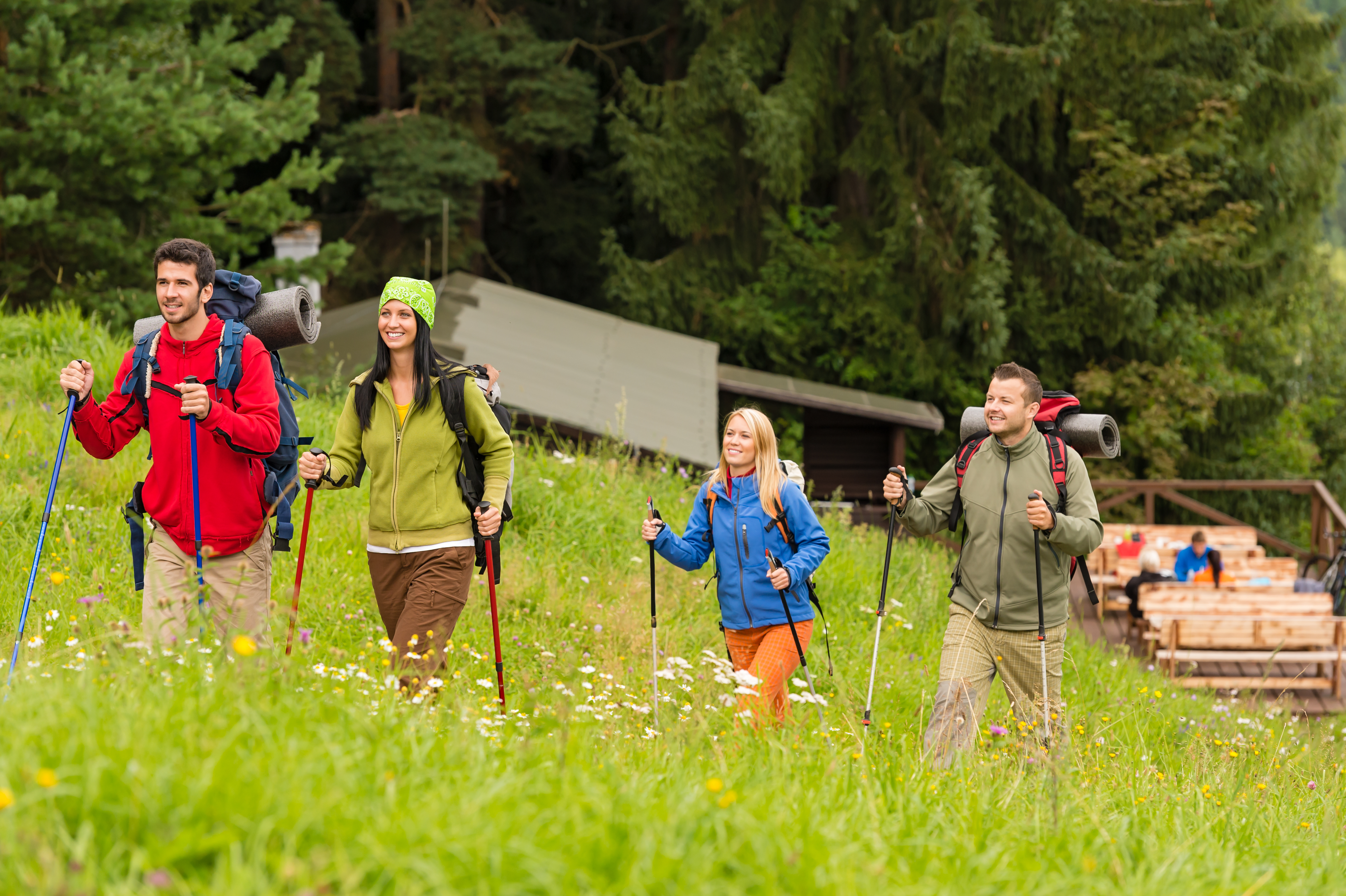 Smiling young people trekking in nature landscape with sticks